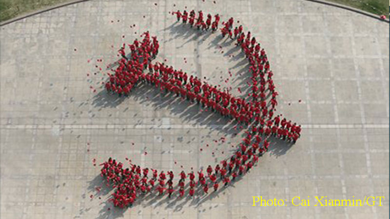 Nearly 260 new Communist Party of China (CPC) members from Fudan University create an 18-meter-long party emblem to mark the upcoming 18th National Congress of the CPC. Photo: Cai Xianmin/GT